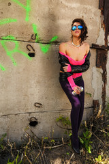 Young beautiful woman in sunglasses with spray paint at wall background