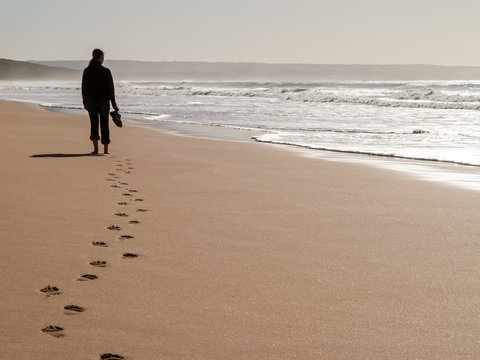Silhouette of a woman walking alone at the beach feeling lonely leaving footprints on the wet sand