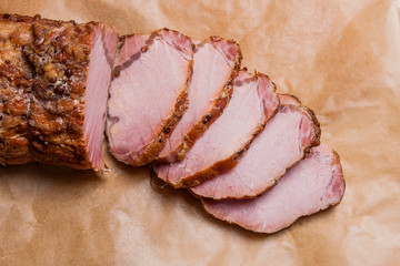 Close up view of sliced smoked meat or ham on brown packing pape