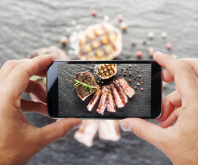 Taking photo of beef steak by smartphone.