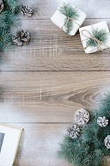 Christmas decorations, pine needles and cones on white wooden background