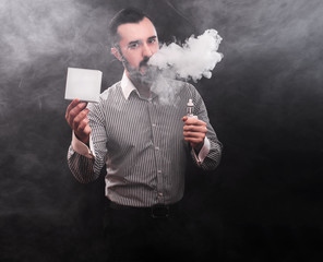 Man is vaping and holding box. Black background.