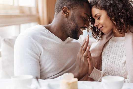 Passionate African American couple touching hands in the cafe