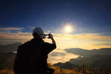 Tourist man takes a photo of beautiful landscape with mobile pho