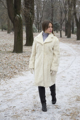 A beautiful young woman walking alone in the park