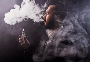 Man using vaporizer or e-cigarette. Black background.