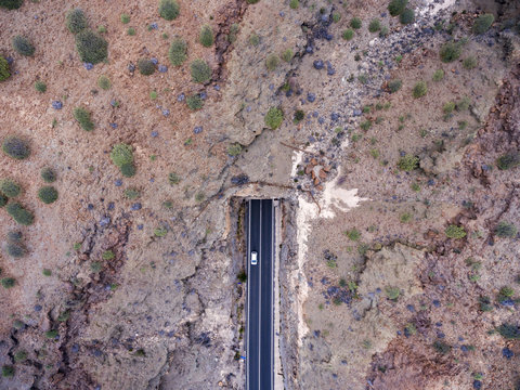 Aerial view of car entering mountain tunnel