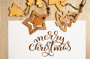 Wooden toys on white background with text Merry Christmas. Calligraphy lettering