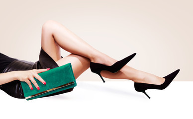 Wall Mural - Beautiful legs woman with green purse and black heels shoes sitting on the white table. Copy space on the light beige background.