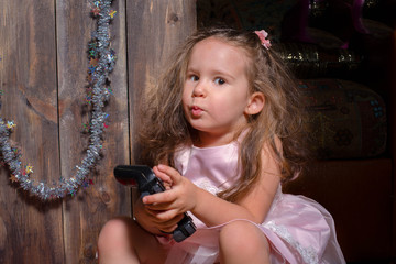 little beautiful girl in pink dress sitting by the Christmas tree and waiting for Santa Claus and many gifts. Christmas decorations everywhere
