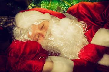 Tired Santa Claus sleeping under the Christmas tree.