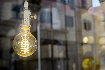Decorative old edison style light bulb against defocused urban scene reflecting background