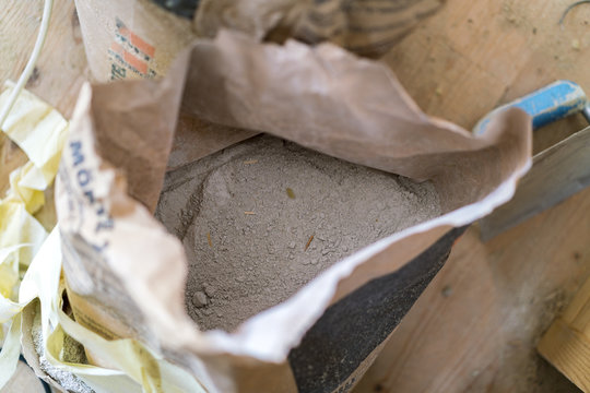 Opened bag of dry cement viewed from above on a building site in a construction or renovation concept