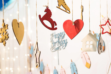 Happy birthday colored figurines icons signs on ropes. Snow flake and heart, horse, star, house, glove, star, feather