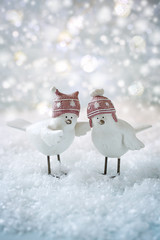 Two funny little birds on a Christmas background. Christmas card.