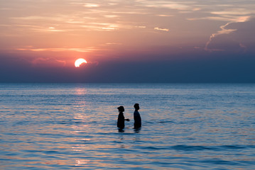 Romantic couple in the sea during sunset