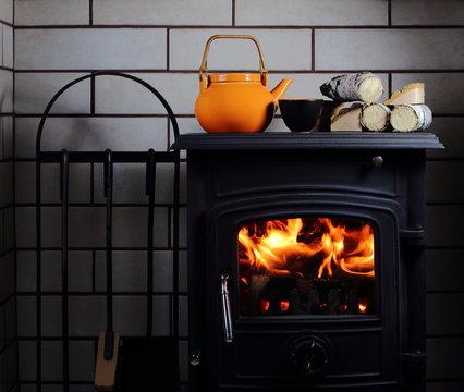 чайник и чашка с чаем на камине с дровами