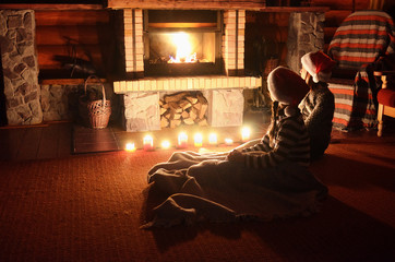 Christmas and New Year holidays, children in santa hats near fireplace in wooden house, kids have fun