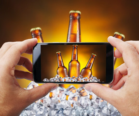 Taking photo of beer bottles in ice by smartphone.