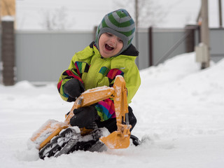 Cute cheerful child dressed in winter overalls playing excavator on white snow