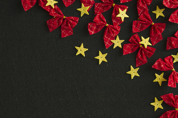 Red bows and yellow gold stars on black background