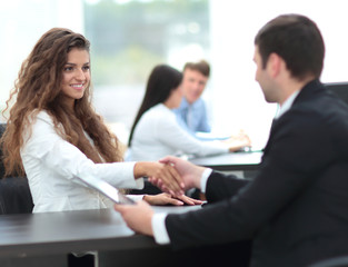 beautiful female Manager shaking hands with a client at the work