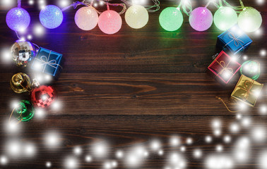 Christmas light and gift ornaments on old wood background.