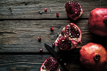Fresh pomegranates on a wooden background. Organics, fruit, food