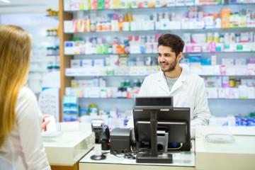 Experienced pharmacist counseling female customer in modern phar