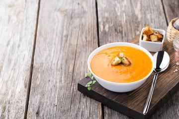 Pumpkin carrot soup on wooden background