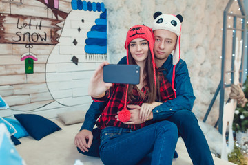 Beautiful young couple in funny hats sitting on the background of Christmas decorations and make selfie.