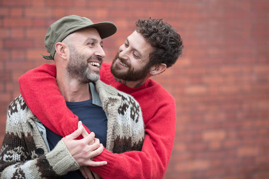 Gay couple cuddling and laughing in front of brick wall