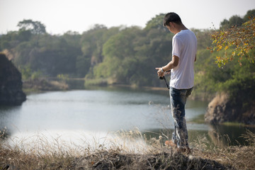 Handsome guy wearing white t-shirt and jeans, holding a camera at mountain peak,lake front