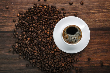 Coffee cup and beans on dark wooden table. Top view