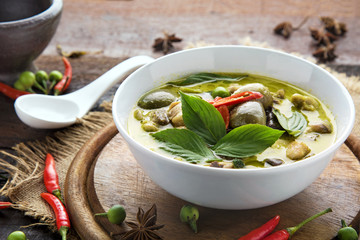 Thai food chicken green curry on dark wooden background.