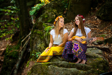Two young girls with guitar in a summer forest