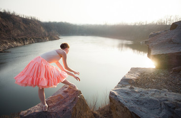 Ballerina in ballet pose above the lake