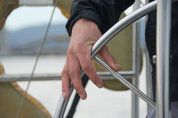 Man's hand on the steering wheel sailboat