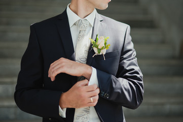 Groom buttons his shirt at the wedding