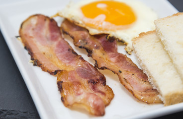 Fried egg and bacon slices plate