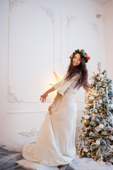 Beautiful girl in white dress and wreath on her head dancing on