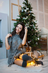 Happy smiling girl in a gray dress sits near a Christmas tree