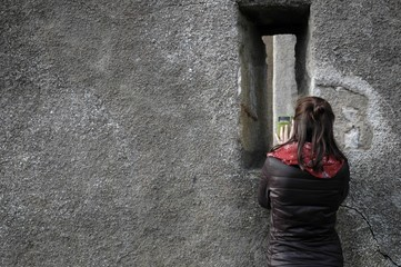 Curious woman taking a photo on a mobile phone of the inside of a castle wall.