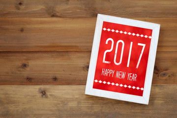 Happy new year 2017 on white vintage wooden frame on wood