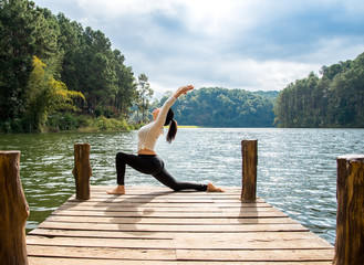 Healthy woman practicing yoga on the bridge in the nature.