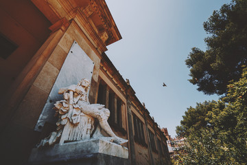 Marble statue of sitting man near facade of old historical building in park of Barcelona with flying pigeon behind, sunny summer day, Spain