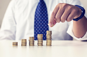 Business man's hand put money coins to stack of coins. Money, Financial, Business Growth concept,