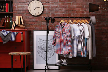 Casual stylish shirts on hanger stand in room