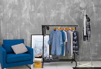 Casual stylish male shirts on hanger stand in room