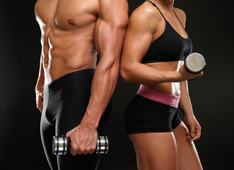 Sporty young couple with dumbbells on black background, closeup